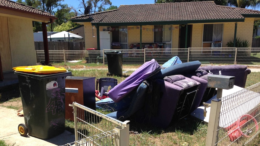 Furniture and rubbish bins fill the front yard of an abandoned home in the western Sydney suburb of Bidwill.
