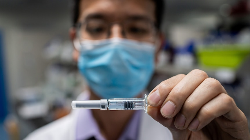 A man wearing a blue face mask holds up a vial of experimental COVID-19 vaccine.