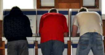 Three men vote at a polling station.