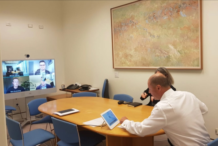 A man does a Zoom meeting in the office