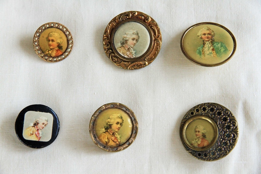 Six buttons featuring faces, on a white background.
