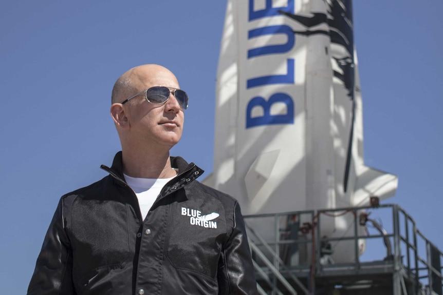 Billionaire Jeff Bezos wearing aviator sunglasses standing in front of a rocket