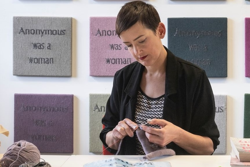 "The artist Kate Just knitting with panels in the background that read ""anonymous was a woman"""