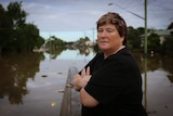 A woman stands in front of flood waters in Lismore.