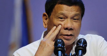 Rodrigo Duterte holds two fingers against his cheek as he speaks into microphones at a press conference.
