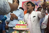 Men stand behind a table with a large birthday cake. A poster of Donald Trump is in the background.