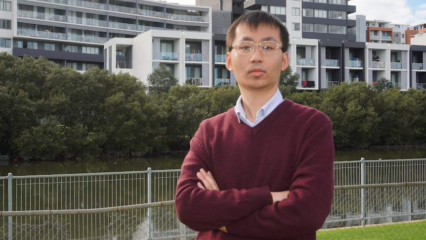 A man poses in front of units