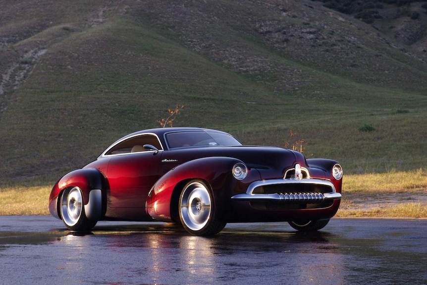 A dark maroon concept vehicle on a wet road in front of a background of hills.