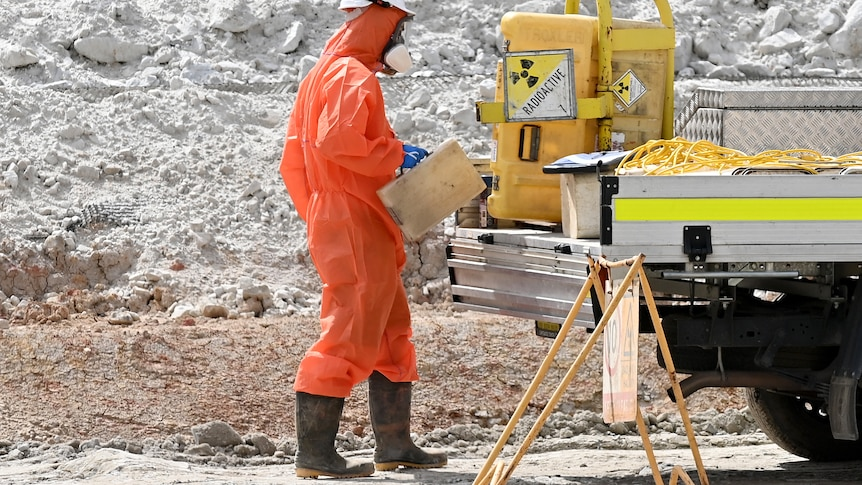 A worker in protective clothing stands on a dirt site at a ute