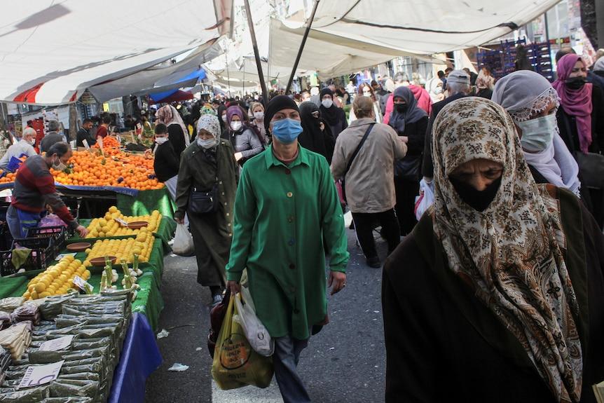 人们戴着口罩购物在一个新鲜食品市场上。