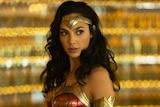 Gal Gadot in Wonder Woman costume and hair out, with sparkling backdrop blurred in background.