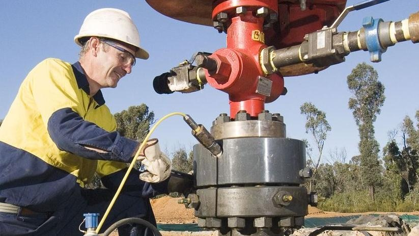 A worker fiddles with a coal seam gas drill.