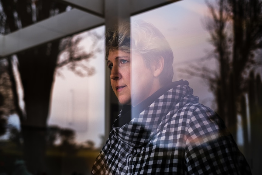 Renee Pickles looking out her kitchen window with dark shadows cast across her face from the reflection