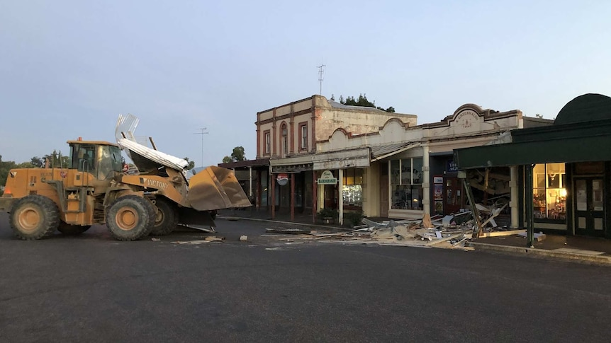 A front-end loader stands in front of a shopfront that has been smashed in.