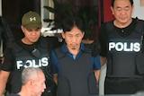 Ri Jong-chol leaves a Malaysian police station alongside police.