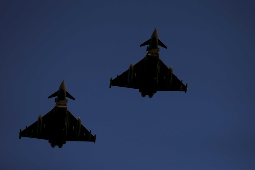 Two RAF Typhoon fighter jets fly through a blue sky