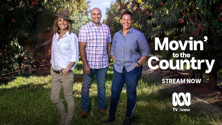 Two women and a man stand smiling in a peach orchard, with 'Movin' To The Country' written beside them