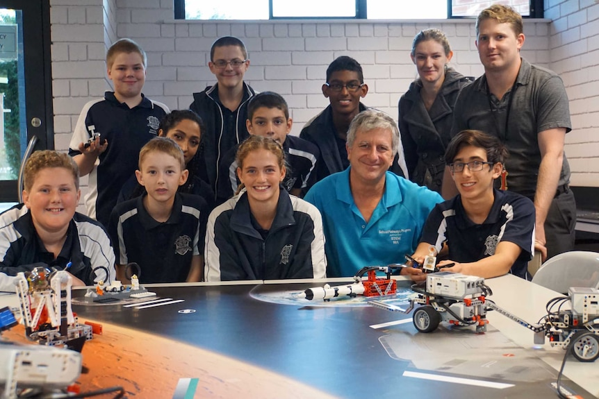 A group of school students with their teacher and robots they have made.