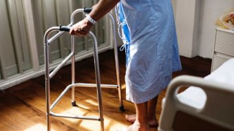 A person wearing a blue hospital gown with a walking frame.