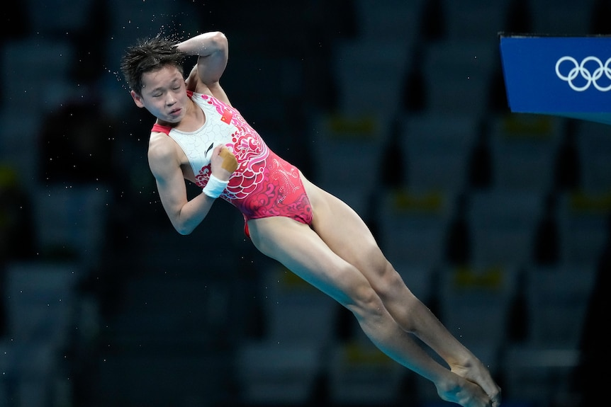 A diver in a red swimsuit poses mid air