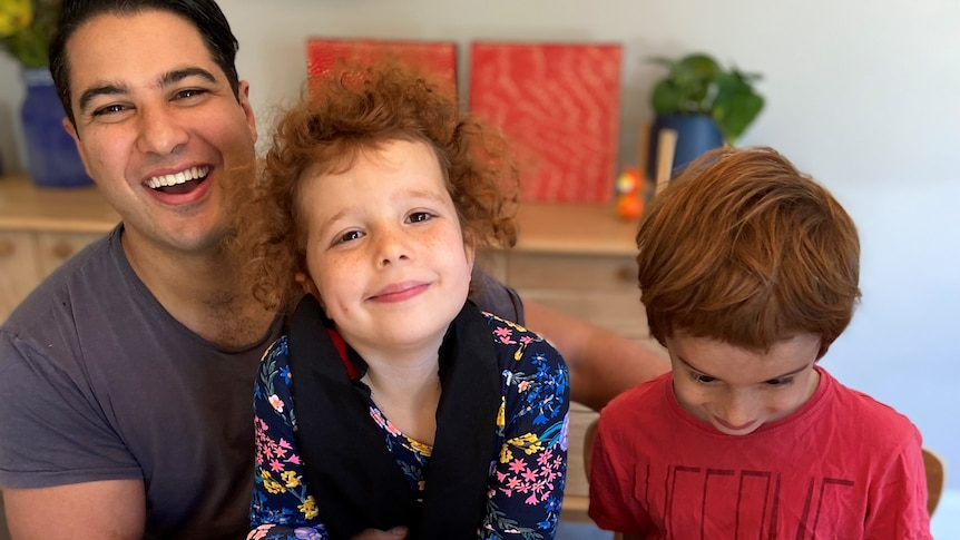 Marc Fennell and two young kids sit at a dining room table with plates of cupcakes, smiling.