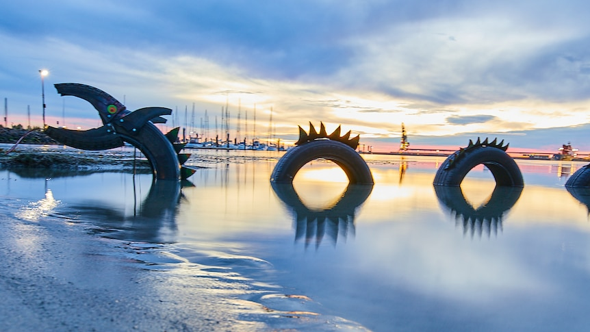 a recycled tyre sculpture of the loch ness monster sits in shallow water