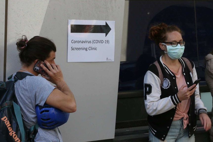 Two people stand outside a sign pointing to a coronavirus screening clinic