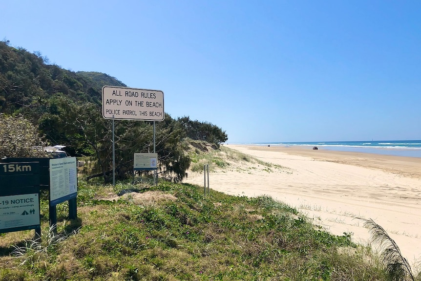A stretch of beach with a road rules sign