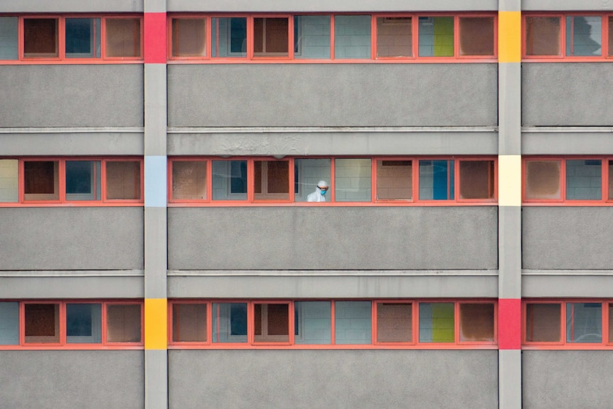 You view rectilinear windows with red borders across three storeys on a modernist public housing tower.