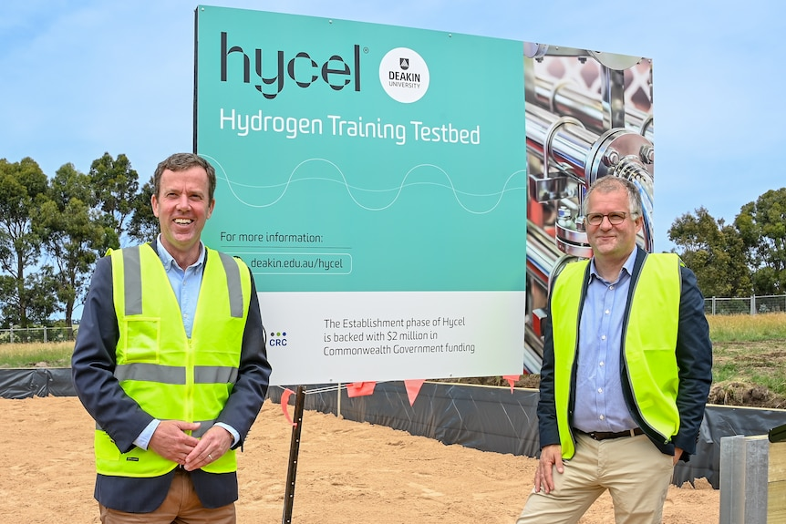 Two men wearing high vis jackets looking at the camera in front of a sign and construction site.