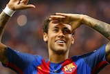 Neymar, while playing for Barcelona, celebrates a win by gesturing to the crowd.