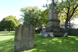A tombstone and mausoleum in the green surrounds of North Hobart cemetery.