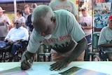 "A man wearing a ""treaty now"" tshirt signs."