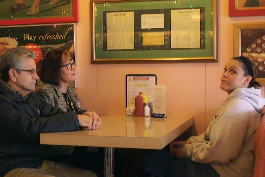 A thirty-something woman sits opposite her parents in a diner booth, looking fed up as they look at her.