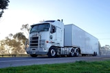 A white truck drives a long a highway at a golden sunrise, passing large gum trees.