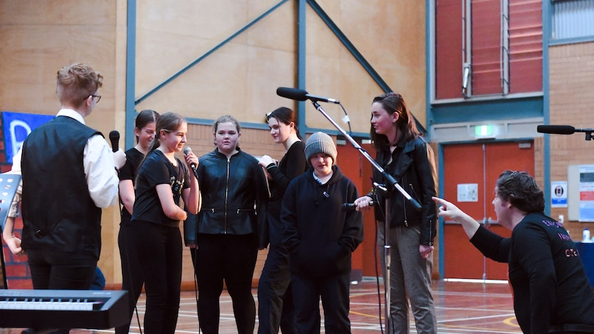 Group of teenage students get dressed rehearsing a musical on stage as the director crouches in front