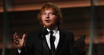 Ed Sheeran happily accepts award on stage.