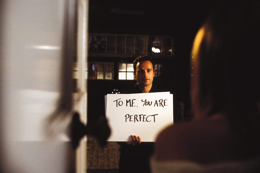"Screen shot from Love Actually movie where Andrew Lincoln holds a card saying ""To me, you are perfect"""
