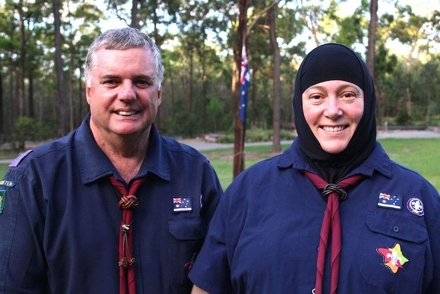 Two scout leaders in a forested parkland in front of a building