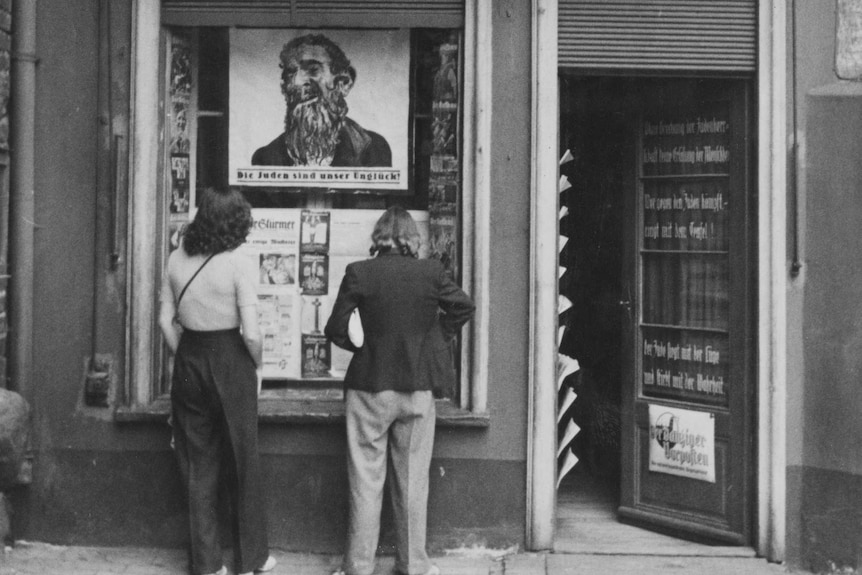 Two people stand outside a newspaper office. An illustration of a bearded jewish man is on a poster in the window.