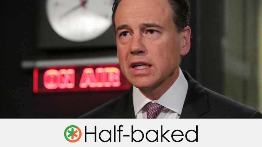 """The Minister in a radio studio. """"Half-baked"""" is written at the bottom of the frame."""