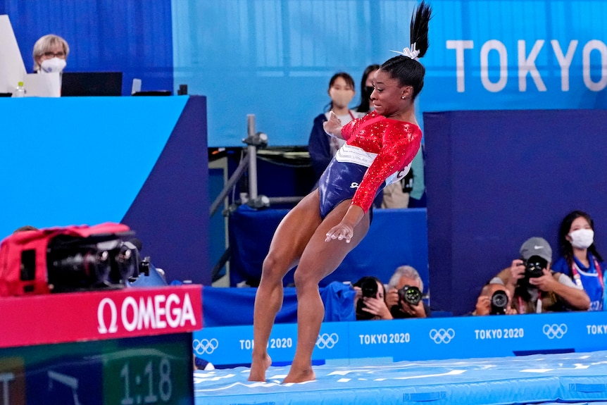 A woman in a leotard lands on a blue mat, her right ankle bent slightly