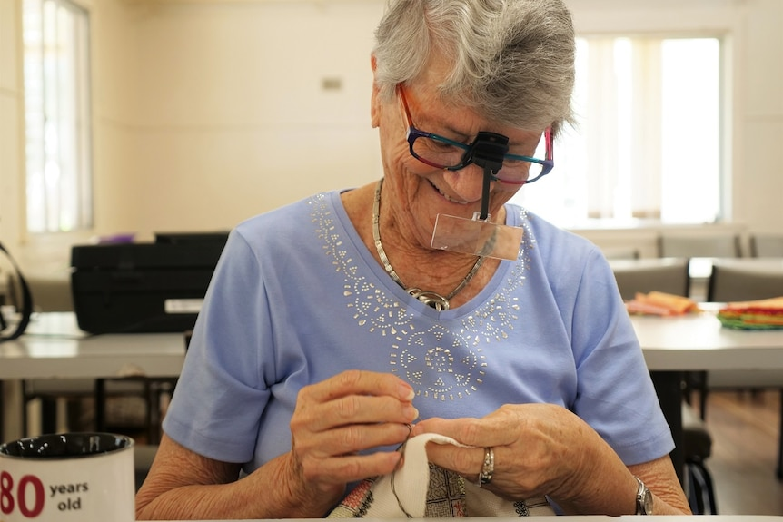 Caroline Holmes wearing a light blue shirt, glass with a special magnifying extension, smiles while embroidering.