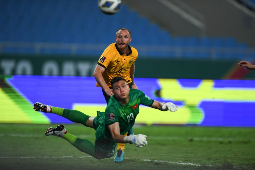 Rhyan Grant watches as the ball sails past the Vietnamese goalkeeper, who is diving backwards and looking at the ball
