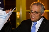 Scott Morrison holds up a document during a night-time press conference at the Lodge