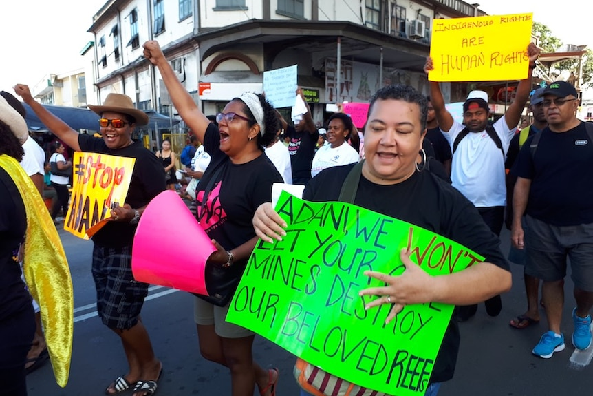 A stop Adani protest in Fiji held in 2017. They are marching through town, chanting and holding posters.