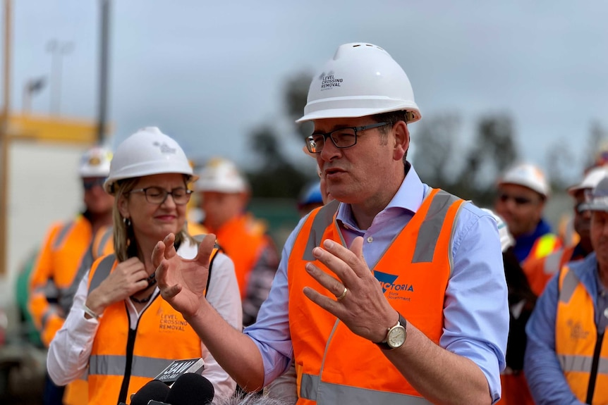 A man in a blue shirt and orange high-vis jacket and hard hat holds his hands out as he addresses the media.