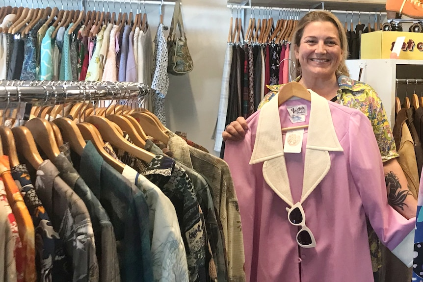 A woman holds up a pink coat surrounded by racks of clothing
