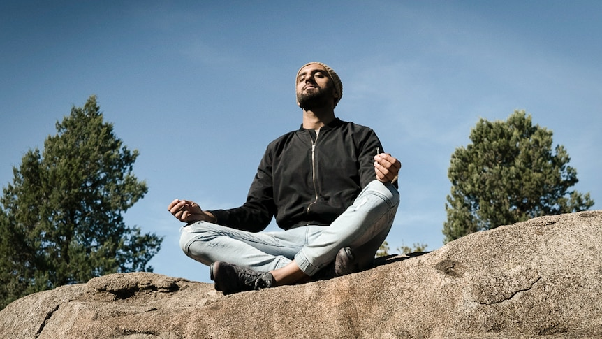 Zohab Zee Khan sitting in meditation on top of a large rock depicting our 7 easy ways to start meditating.