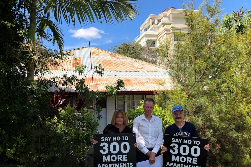 Three unhappy people stand outside an old cottage with a rusty roof carrying signs protesting development